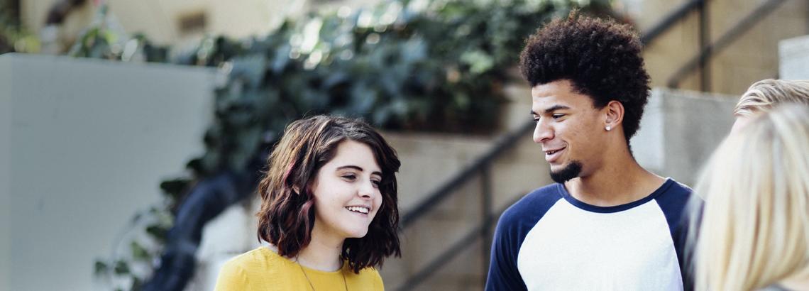 Drei junge Menschen stehen zusammen und unterhalten sich, die beiden Personen, die man frontal sieht. lächeln und sehen glücklich aus.