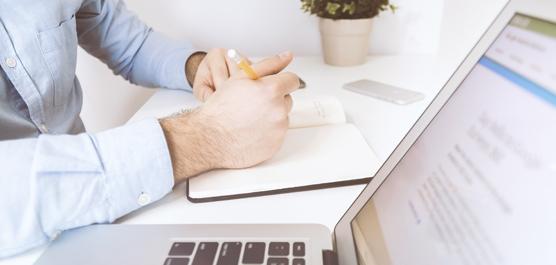 Sitzender Mann beim Schreiben, daneben aufgeklappter Laptop.
