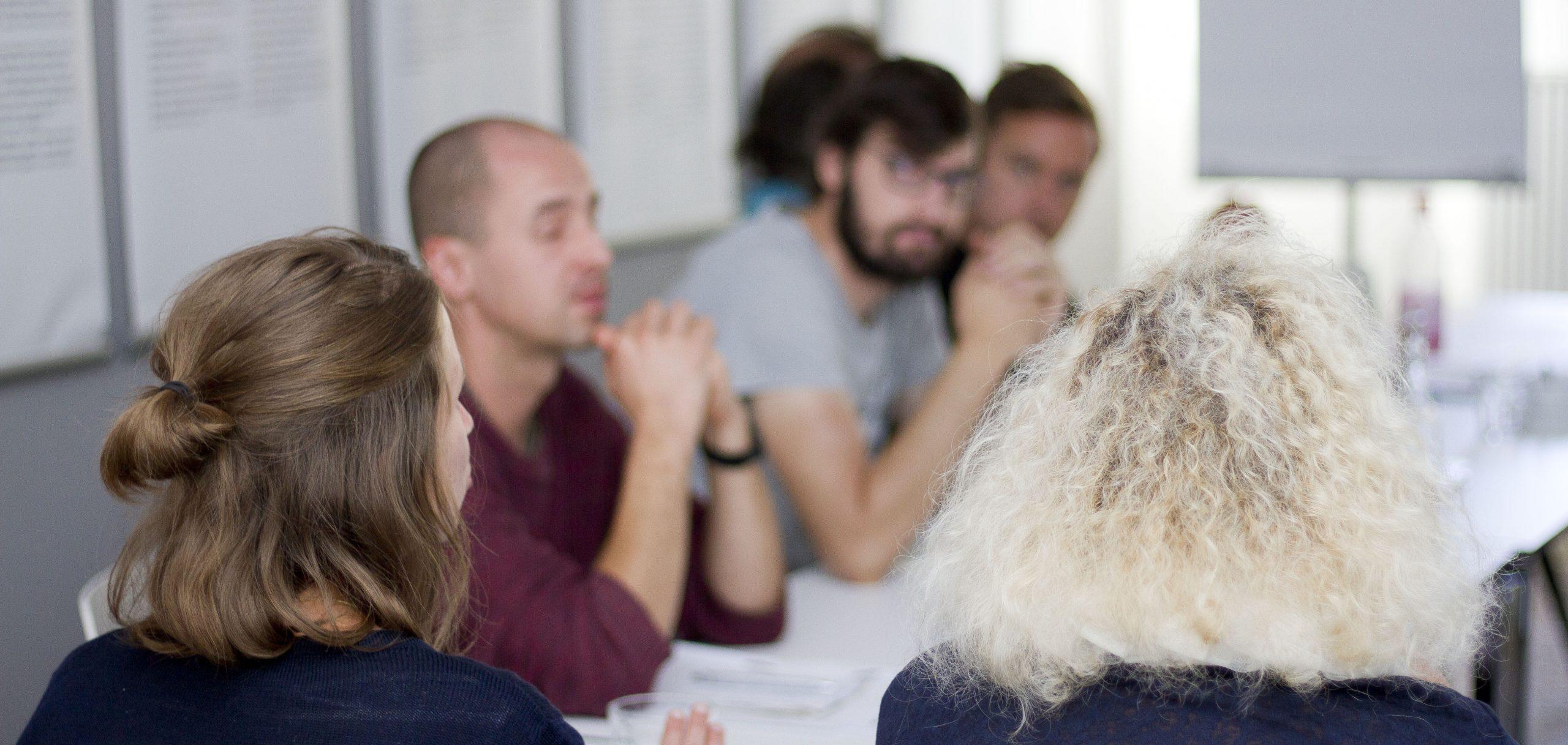 Verschiedene Menschen während eines Workshops am Tisch sitzend