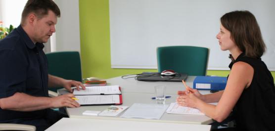 Junge Frau berät einen interessierten Mann zum Ehrenamt. Beide sitzen sich an einem Tisch gegenüber .