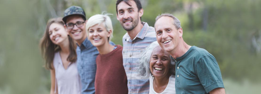 Sechs Menschen (alt und jung, männlich und weiblich, verschiedene Hautfarben) stehen Arm in Arm und blicken lächelnd in die Kamera.