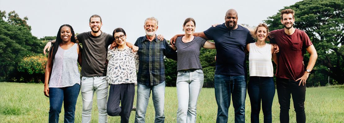 Acht Menschen (alt und jung, männlich und weiblich, verschiedene Hautfarben) stehen Arm in Arm und blicken lächelnd in die Kamera.