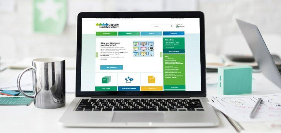 """Aufgeklappter Laptop, Bildschirm zeigt Homepage der """"Digitalen Nachbarschaft""""."""