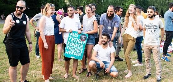 """Mehrere junge Menschen stehen zusammen auf einer Wiese und halten ein Plakat, auf dem steht """"Aus Fremden können Freunde werden""""."""