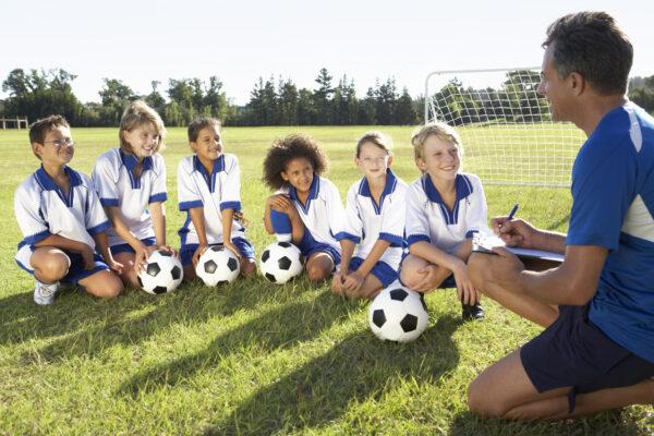 Ein Mann trainiert eine Gruppe von Kindern auf einem Fußballfeld.