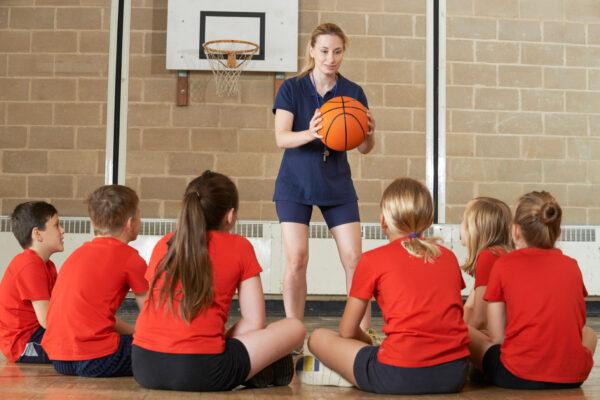 In einer Sporthalle erklärt eine Frau sechs Kindern Basketball-Regeln.