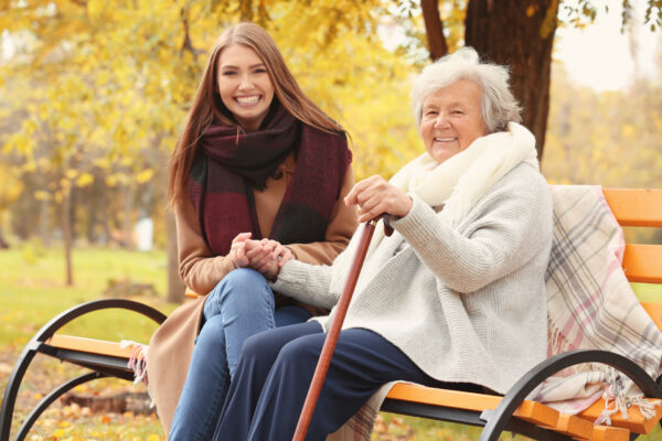Junge Frau und ältere Frau sitzen lächelnd nebeneinander auf einer Parkbank. Die junge Frau hält die Hand der älteren Frau.
