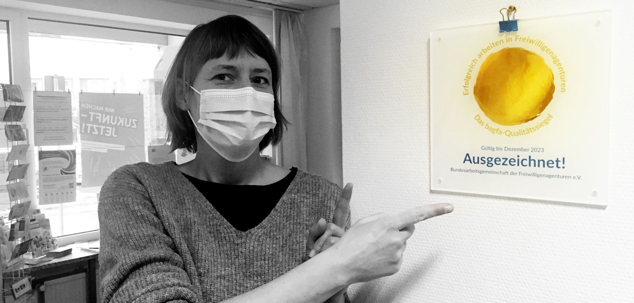 Eine Mitarbeiterin der Freiwilligen-Agentur zeigt auf die Plakette mit dem Qualitätssiegel der Bagfa.