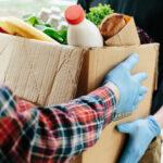 Ein Mensch übergibt eine Kiste voller Lebensmittel an einen anderen Menschen. Beide tragen Gummihandschuhe.
